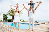 Parents carrying children on shoulders at luxury poolside Stock Photo - Premium Royalty-Freenull, Code: 6113-07159491