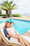 Grandmother and granddaughter relaxing at poolside Stock Photo - Premium Royalty-Free, Artist: Blend Images, Code: 6113-07159495