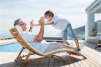 rich lifestyle - Grandfather and grandson playing at poolside Stock Photo - Premium Royalty-Freenull, Code: 6113-07159507