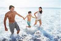 Family playing in waves at beach Stock Photo - Premium Royalty-Freenull, Code: 6113-07159531