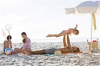 preteen girl topless - Family relaxing together on beach Stock Photo - Premium Royalty-Freenull, Code: 6113-07159550