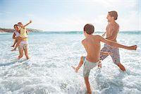 Family playing together in waves on beach Stock Photo - Premium Royalty-Freenull, Code: 6113-07159568