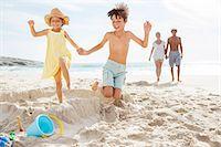 pre-teen beach - Children kicking down sandcastle on beach Stock Photo - Premium Royalty-Freenull, Code: 6113-07159586