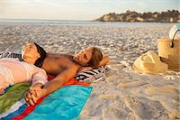 Couple relaxing together on beach Stock Photo - Premium Royalty-Freenull, Code: 6113-07159640