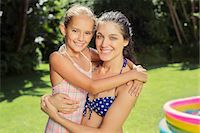 Mother and daughter hugging in backyard Stock Photo - Premium Royalty-Freenull, Code: 6113-07159716