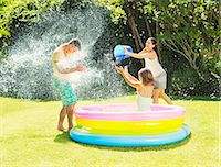 family  fun  outside - Family tossing water on father in backyard Stock Photo - Premium Royalty-Freenull, Code: 6113-07159731
