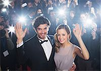 Celebrity couple waving on red carpet with paparazzi in background Stock Photo - Premium Royalty-Freenull, Code: 6113-07159890