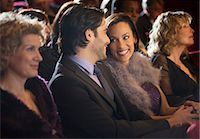 Smiling couple talking in theater audience Stock Photo - Premium Royalty-Freenull, Code: 6113-07159995