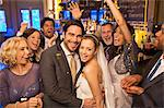 Friends cheering around smiling bride and groom at wedding reception Stock Photo - Premium Royalty-Free, Artist: Blend Images, Code: 6113-07160029