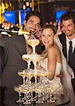 Groom pouring champagne pyramid at wedding reception Stock Photo - Premium Royalty-Free, Artist: Blend Images, Code: 6113-07160033