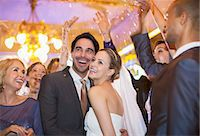 Friends throwing confetti over bride and groom at wedding reception Stock Photo - Premium Royalty-Freenull, Code: 6113-07160040