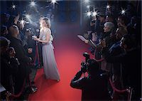 Well dressed female celebrity signing autographs and posing for paparazzi on red carpet Stock Photo - Premium Royalty-Freenull, Code: 6113-07160054