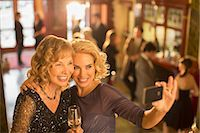 Well dressed women with champagne taking self-portrait with camera phone in theater lobby Stock Photo - Premium Royalty-Freenull, Code: 6113-07160057