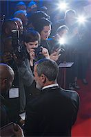 Well dressed male celebrity signing autographs at red carpet event Stock Photo - Premium Royalty-Freenull, Code: 6113-07160059