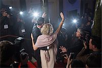 Rear view of well dressed celebrity couple waving to paparazzi on red carpet Stock Photo - Premium Royalty-Freenull, Code: 6113-07160064