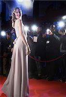 Well dressed female celebrity posing for paparazzi on red carpet Stock Photo - Premium Royalty-Freenull, Code: 6113-07160073
