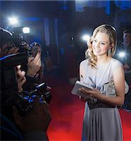 Well dressed female celebrity signing autograph and posing for paparazzi on red carpet Stock Photo - Premium Royalty-Freenull, Code: 6113-07160082