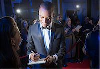 Well dressed celebrity signing autograph on red carpet Stock Photo - Premium Royalty-Freenull, Code: 6113-07160085