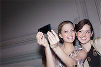 Smiling women taking self-portrait with camera phone Stock Photo - Premium Royalty-Freenull, Code: 6113-07160111