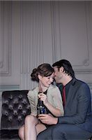 Well dressed couple drinking champagne and cuddling Stock Photo - Premium Royalty-Freenull, Code: 6113-07160114