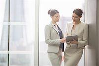 Businesswomen using digital tablet in office Stock Photo - Premium Royalty-Freenull, Code: 6113-07160431
