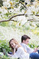 Couple using digital tablet and cell phone in park Stock Photo - Premium Royalty-Freenull, Code: 6113-07160622