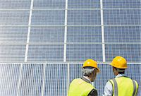solar power - Workers examining solar panels in rural landscape Stock Photo - Premium Royalty-Freenull, Code: 6113-07160896