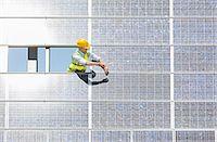 solar power - Worker examining solar panel in rural landscape Stock Photo - Premium Royalty-Freenull, Code: 6113-07160917