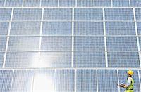 solar power - Worker examining solar panel in rural landscape Stock Photo - Premium Royalty-Freenull, Code: 6113-07160930