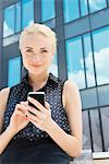 Young businesswoman using smartphone outdoors