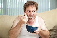 Unemployed man sitting on the couch eating cereal as he watches television. Stock Photo - Royalty-Freenull, Code: 400-07165107