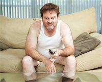 Unemployed man sitting home watching TV, bored and discouraged. Stock Photo - Royalty-Freenull, Code: 400-07165108