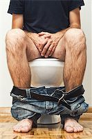 Man sitting on toilet with his pants down. Stock Photo - Royalty-Freenull, Code: 400-07169176