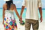Young couple holding hands on tropical beach.