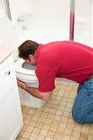 Man kneeling down in the bathroom, vomiting into the toilet. Stock Photo - Royalty-Freenull, Code: 400-07180000