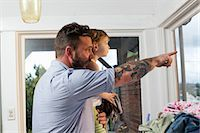 Father and daughter looking through window Stock Photo - Premium Royalty-Freenull, Code: 614-07194440