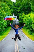 Teenage girl jumping with umbrella on road, Bainbridge Island, Washington, USA Stock Photo - Premium Royalty-Freenull, Code: 614-07194649