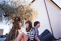Brother and sister sitting back to back, laughing Stock Photo - Premium Royalty-Freenull, Code: 614-07194693