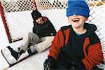 Two Boys Sitting in Hockey Net on Outdoor Ice Rink, Laughing Stock Photo - Premium Rights-Managed, Artist: Mick Ritzel, Code: 700-07199509