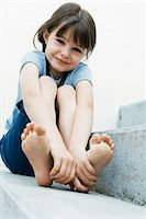 Portrait of Girl Sitting Outdoors Holding Feet Stock Photo - Premium Rights-Managednull, Code: 700-07199531