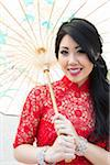 Close-up portrait of young woman holding Chinese parasol, smiling and looking at camera, Ontario, Canada Stock Photo - Premium Rights-Managed, Artist: Ikonica, Code: 700-07199849