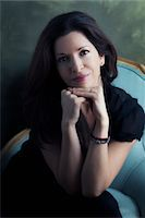 Portrait of Mature Woman sitting in Chair leaning on Hands, Studio Shot Stock Photo - Premium Rights-Managednull, Code: 700-07199905