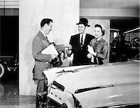 1950s COUPLE BUYING NEW CAR FROM AUTOMOBILE SALESMAN HANDING OVER THE KEYS Stock Photo - Premium Rights-Managednull, Code: 846-07200064