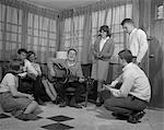 1950s 1960s GROUP OF YOUNG TEENAGERS GATHERING AROUND BOY PLAYING GUITAR