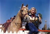 1940s 1950s SMILING YOUNG BLONDE COWGIRL SITTING ON FENCE POSING BY PALOMINO HORSE HOLDING BUNCH OF CARROTS LOOKING AT CAMERA Stock Photo - Premium Rights-Managednull, Code: 846-07200117