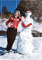 1940s 1950s SMILING TEEN GIRL POSING LEANING AGAINST SNOWMAN LOOKING AT CAMERA LOOKING AT CAMERA Stock Photo - Premium Rights-Managednull, Code: 846-07200134