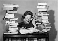 release - 1950s WOMAN SITTING BETWEEN STACKS OF BOOKS PULLING DOWN GLASSES TO LOOK OVER RIMS Stock Photo - Premium Rights-Managednull, Code: 846-07200139