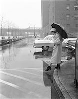 people with umbrellas in the rain - 1950s WOMAN IN RAIN COAT HAT BOOTS HOLDING  UMBRELLA CROSSING CITY STREET IN WET FOUL WEATHER Stock Photo - Premium Rights-Managednull, Code: 846-07200143