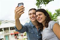 A young couple side by side, flirting and taking photographs. Stock Photo - Premium Royalty-Freenull, Code: 6118-07203274