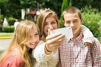 farm phone - Three young people, two girls and a boy, posing and taking selfy photographs. Stock Photo - Premium Royalty-Freenull, Code: 6118-07203278